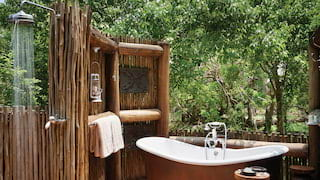 Open-air safari lodge bathroom with a copper standalone bathtub and rain shower