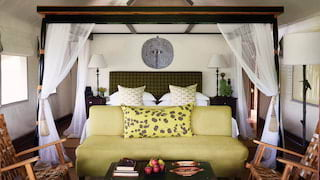 Luxurious safari lodge room with four-poster bed and lime green sofa