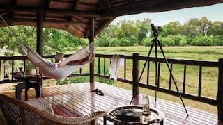 Lady relaxing in a hammock on a safari lodge terrace overlooking the savannah