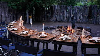 Candlelit dining tables arching around a circular campfire in a shaded clearing