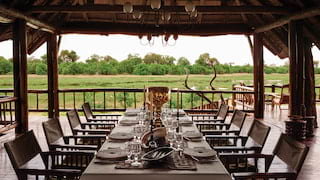 Linen-coated banquet table in an open-air dining lodge overlooking the savannah
