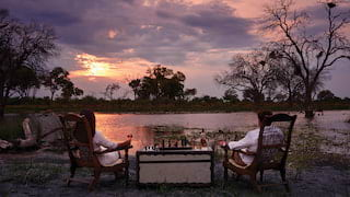 A couple at a private dining table overlooking a safari watering hole at sunset