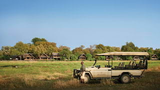 Gamekeeper perching on a safari rover with luxury lodges in the background