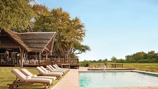 Outdoor pool surrounded by sun beds next to a thatch roof safari lodge