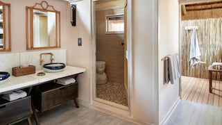 Luxurious safari lodge bathroom with outdoor rain shower and light, warm accents