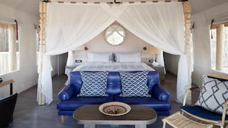 Four-poster bed with white silky drapes and a blue leather sofa in front