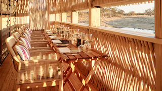 Wooden raised hideout overlooking a watering hole and set for a formal dinner
