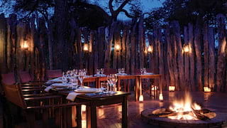 Sunken fire pit surrounded by curved formal dining tables lit by lanterns