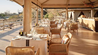 Restaurant veranda furnished with stylish rattan chairs and linen-coated tables