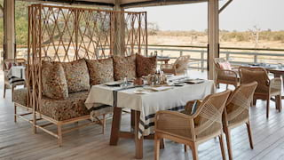 Open-air restaurant with polished wooden deck floor and rattan furnishings