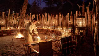 Banquet table in a semicircle with a firepit in the middle lit by lanterns