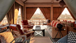 Open-air lodge lounge with canvas curtains and plush furnishings