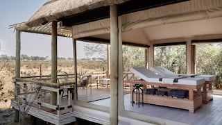 Two massage tables in an open-air spa hut overlooking grasslands