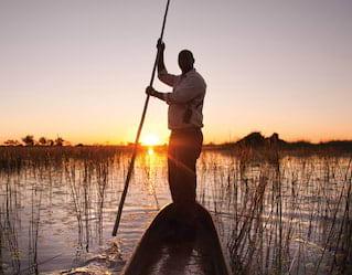 Uomo che attraversa le zone umide su una tradizionale canoa mokoro