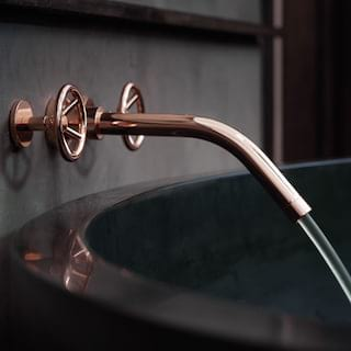 Close-up of a black polished bathtub with rose-gold taps