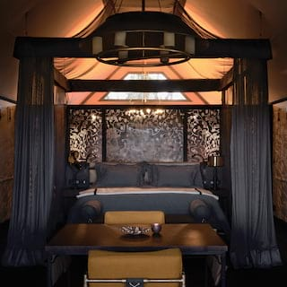Safari lodge tent with a grand four-poster bed in mustard and dark grey accents