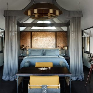 Glamorous safari tent room with a four-poster bed with yellow and light blue accents