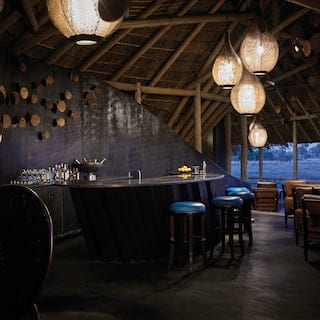 Stylish open-air bar with atmospheric dark wood and navy details and paper hanging lanterns
