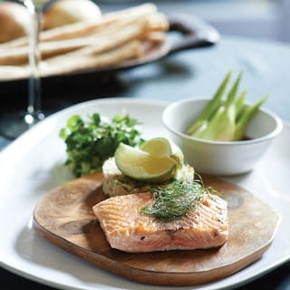 Close-up of smoked salmon and a fish cake on a wooden platter garnished with lime