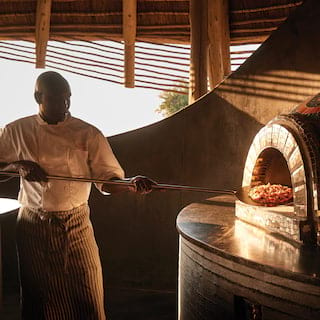 Chef putting a pizza into a stone pizza oven in an open-air restaurant at sunset