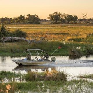 Motorised safari boat sailing across a river delta among grasslands at sunrise