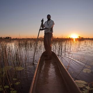 Guide standing on the edge of a mokoro canoe sailing on a river at sunrise