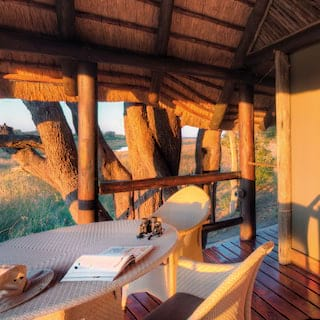 Sunset rays on a wooden safari lodge terrace with a white rattan seating area