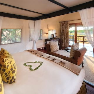 Heart of petals on a four-poster bed in a light and airy safari lodge room