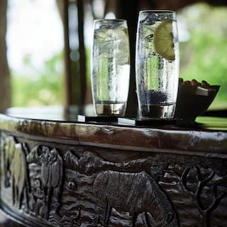 Two tall water glasses with a lime garnish on a polished carved wooden bar top