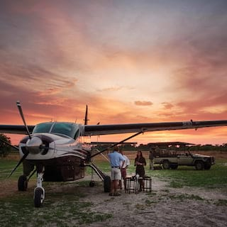 Guests stepping down from a small aircraft under a dramatic sunset