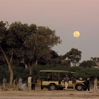 Guests surrounding a safari rover under a full moon at twilight