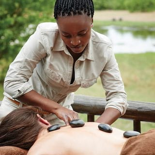 Close-up of a guest receiving a hot stone massage on an open-air spa terrace