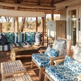 Safari lodge veranda with blue patterned furnishings and glass sliding doors