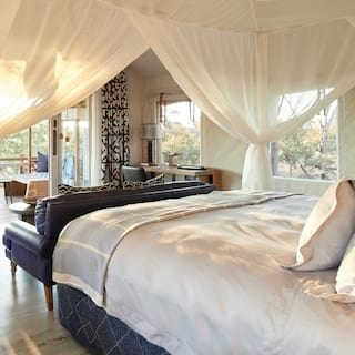 Pillowy four-poster bed with view through a bedroom to a veranda at sunset