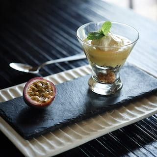 Passion fruit mousse dessert in a glass, served with a slice of passion fruit