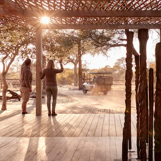 Guests waving from a safari lodge veranda shaded with rustic branches