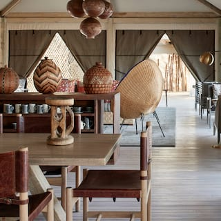 Elegant open-air lounge with khaki and light wood details and African vase details