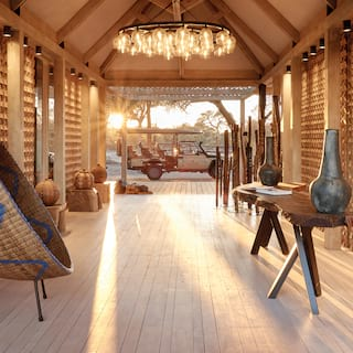 Open-air guest lobby with rustic wood details and a modern chandelier