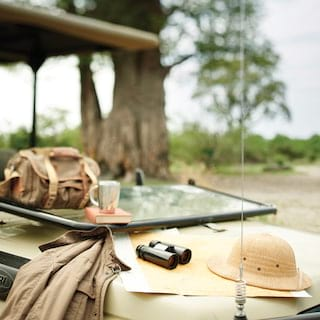 Binoculars, safari hat, jacket and satchel placed on a rover bonnet