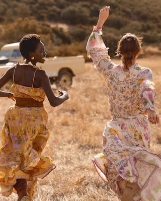 Two ladies running joyfully through grasslands in Botswana