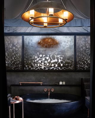 Curved ebony bathtub with rose gold taps and black slate wall tiles