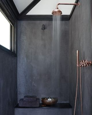 Safari en-suite with a rose-gold rain shower and black slate effect walls