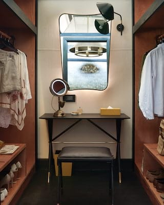 Walk-in wardrobe in a luxurious safari tent with a vanity table and contemporary mirror