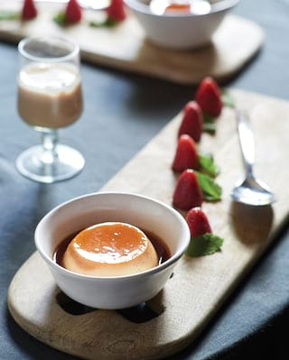 Creme caramel in a white pot served alongside strawberries on a platter