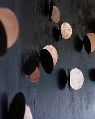 Close-up of a bar wall with dark black walls and copper circle details