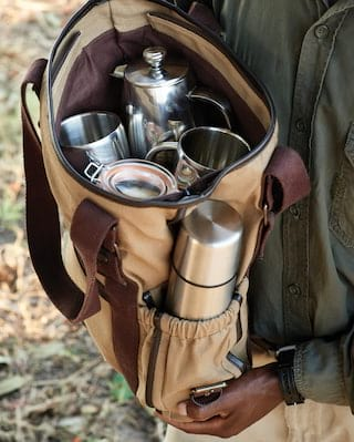 Close-up of a canvas pouch containing silver coffee pot and coffee cups