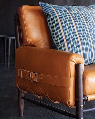 Close-up of a tan leather chair with a blue-patterned cushion