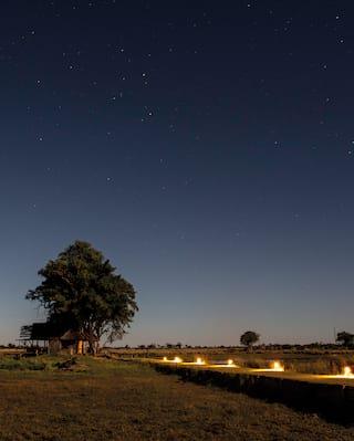 Lantern lit platform over grasslands under a starry sky with sunrise bursting on the horizon