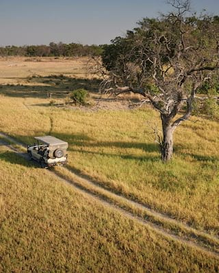 Aerial view of a safari rover driving on a track through grasslands