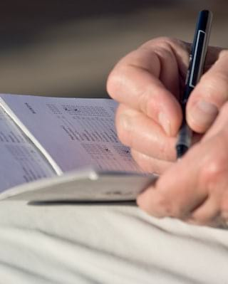 Close-up of a man writing in a pocket book